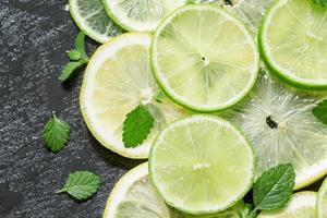 geschnittene Zitronen-, Limetten- und Minzblätter auf dunklem Hintergrund foto
