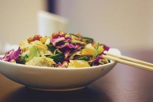 leckerer Gemüsesalat auf Holztisch mit Stäbchen foto