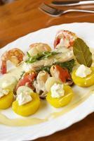 Meeresfrüchte mit Spinat, gelben Kartoffeln und Sahnesauce foto