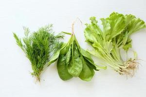 Dill, Spinat und Salat auf weißem Holzhintergrund foto