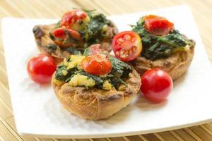 vegetarisches Käsebrötchen mit Spinat und Tomaten.