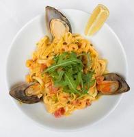 italienische Pasta mit gedünsteten Muscheln und Spinat foto