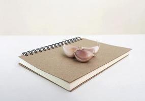 Knoblauch auf dem Notizbuchhintergrund foto