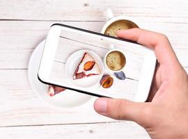 Hände, die Foto Pflaumenkuchen mit Smartphone nehmen