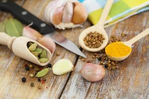 Knoblauch und andere Kochzutaten und Gewürze auf Holzoberfläche foto