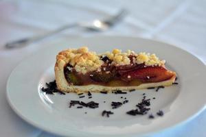 Portion Pflaumenkuchen auf einem weißen Teller foto