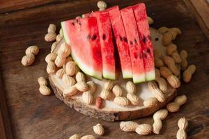 reife rote Wassermelone mit Erdnüssen auf hölzernem Hintergrund foto