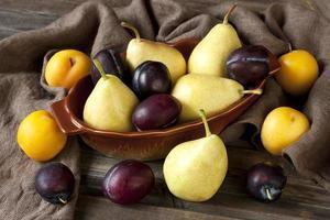 reife Birnen und Pflaumen auf Holztisch foto