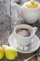 Kaffeetasse schwarz Holzbrett braune Birnen weißer Krug