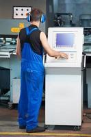 Arbeiter, der CNC-Stanzpresse bedient