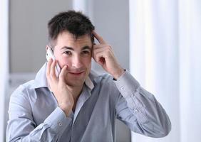 Mann auf Handy im Büro foto