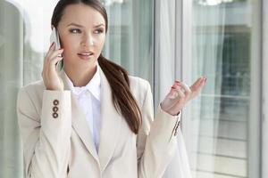 Geschäftsfrau gestikuliert beim Beantworten des Handys foto