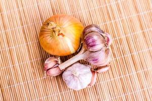Knoblauchzehe und Zwiebel auf Holzhintergrund foto