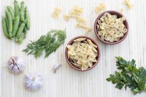 Nudeln in einem Tontopf und grüne Erbsen