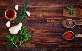 Gewürze und Kräuter auf Holztisch. Draufsicht foto