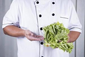 Küchenchef hält Salat foto
