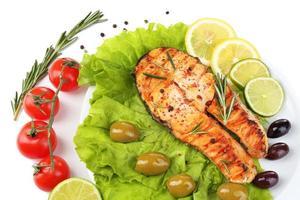 leckerer gegrillter Lachs mit Gemüse, isoliert auf Weiß foto