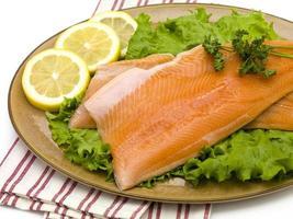 Lachs auf Teller mit Salat und Zitronen foto