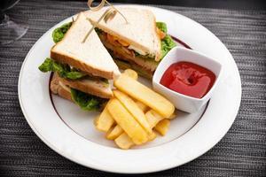 Sandwich mit Spiegeleiern, Speck und Salat