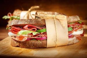 Sandwich mit Speck auf Vintage Holzschneidebrett foto