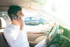 Mann fährt und benutzt Handy foto