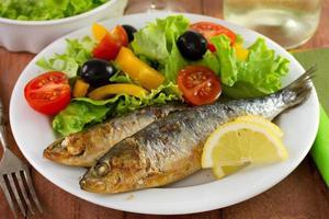 Gebratene Sardinen mit Salat und Zitrone auf dem Teller foto