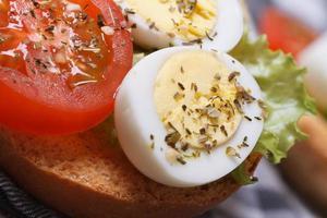 Sandwich mit gekochten Wachteleiern, Tomaten und Salat foto