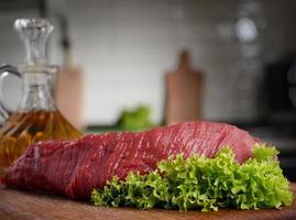rohes Rindfleisch auf einem Schneidebrett mit Salat