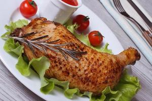 gebratene Hähnchenkeule mit Rosmarin, Salat und Ketchup foto