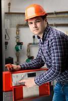 junger Ingenieur, der das System am Bedienfeld einstellt foto