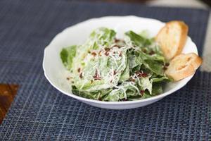 Caesar Salat mit Zwiebelbrot auf blau matt foto