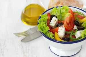 Salat in weißer Schüssel und Öl foto