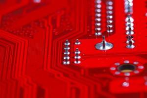 Nahaufnahme der roten elektronischen Hauptplatinenschaltung mit Prozessor foto