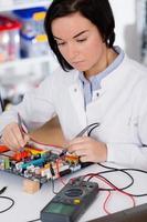 Studentin, die ein elektronisches Gerät mit einem Mikroprozessor studiert foto