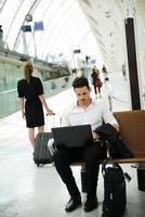 schöner junger Geschäftsmann öffentliche Station mit Computer im WiFi-Bereich foto