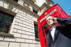 Mann auf Handy rote Telefonzelle foto