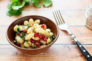 weiße Bohnen in einem Salat mit Koriander und Granatapfel