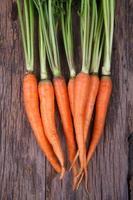 Bündel frischer Karotten mit grünen Blättern über hölzernem Hintergrund