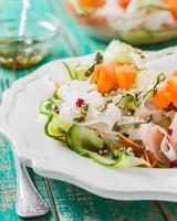 Salat aus Karotten-, Gurken- und Daikon-Rettich auf Holztisch foto