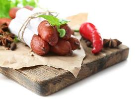 geräucherte dünne Würste mit Salat und Gewürzen isoliert weiß foto