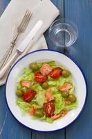 Salat mit Fisch auf weißem Teller foto