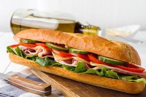 knuspriges Baguette mit Schinken, Gurke, Tomaten, Käse und Salat foto
