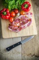 rohes Schweinefleisch auf Schneidebrett und Gemüsemesser. foto