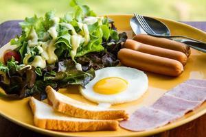 Das Frühstück besteht aus EEG, Salat, Brot, Speck und Wurst foto