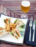 Club Sandwich mit Pommes Frites und einem Bier