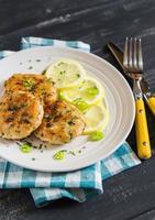 Hühnerschnitzel mit Zitrone und Kräutern auf einem weißen Teller foto