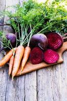 frische Rüben und Karotten auf hölzernem Hintergrund foto