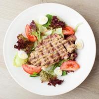 frischer Rindfleischsalat mit Salat, Tomaten, gekochten Eiern, Sauce foto