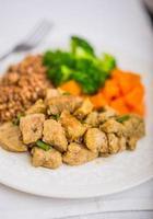 Buchweizen mit Fleisch und Gemüse auf einem weißen Teller
