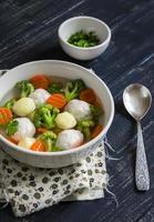 Suppe mit Hühnerfleischbällchen, Kartoffeln, Brokkoli und Karotten foto